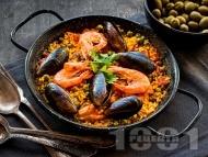 Паеля (ориз) с морски дарове (миди и скариди) в чугунен съд на грил / скара / барбекю